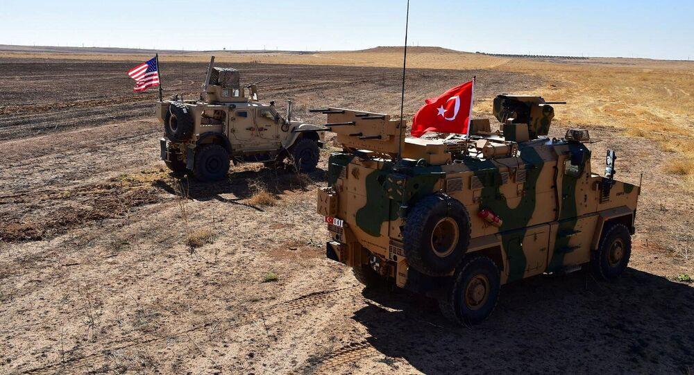 Des véhicules militaires turcs et américains à la frontière syro-turque lors d'une patrouille conjointe