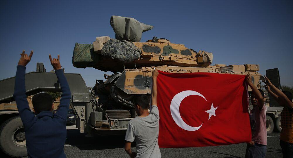 Les Turcs applaudissent un convoi de forces turques transportant des chars vers la frontière syrienne