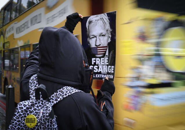 Un manifestant tient un tract demandant la libération de Julian Assange