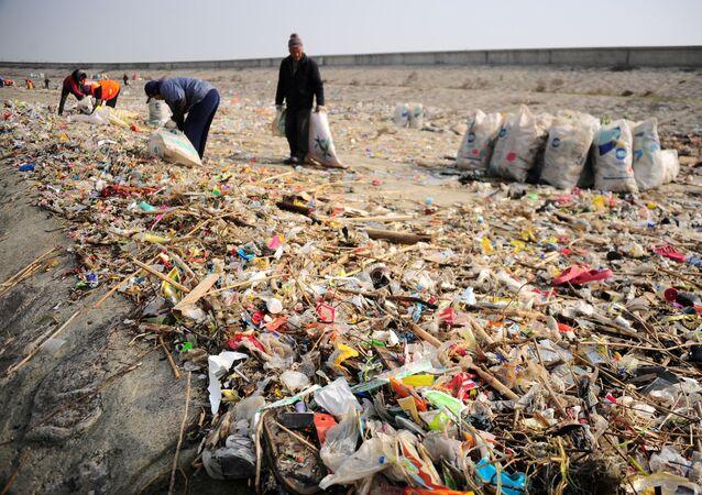 Des travailleurs enlèvent des ordures sur la rive du fleuve Yang-Tsé