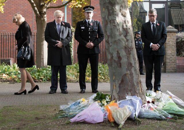 Boris Johnson dépose des fleurs en hommage des victimes mortes dans un camion dans le comté d'Essex, le 28 octobre