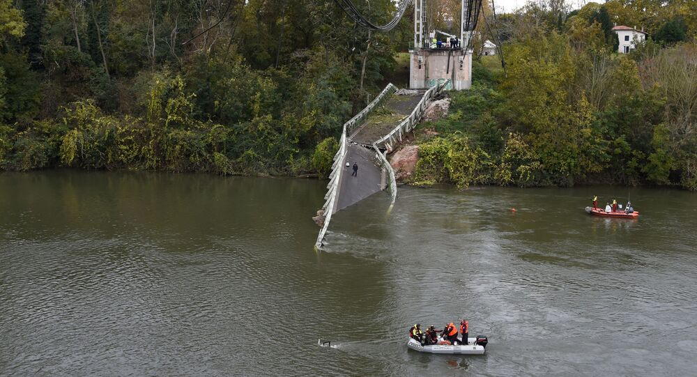 Rescuers sail near a suspension bridge which collapsed on November 18, 2019, in Mirepoix-sur-Tarn, near Toulouse, southwest France.