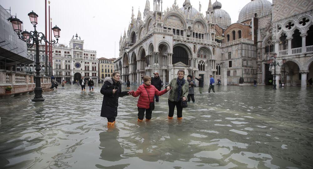 Des gens marchent dans l'eau sur la place Saint-Marc inondée à Venise, en Italie, le mercredi 13 novembre 2019