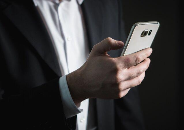 Un homme avec un téléphone (image d'illustration)