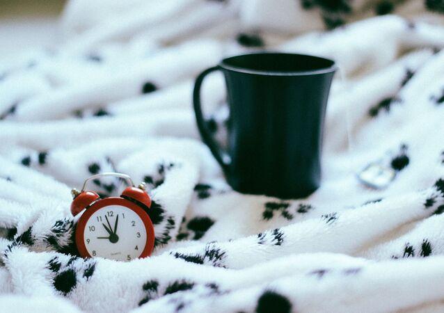 Réveil-matin sur le lit (image d'illustration)