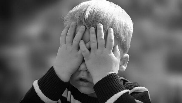 Un enfant cache les yeux  - Sputnik France
