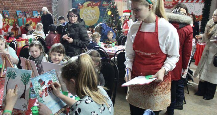 Des enfants dessinent des scènes de Noël sous l'œil vigilant des encadrants