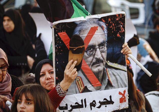 Une femme frappe avec sa chaussure le portrait de Khalifa Haftar lors d'une manifestation contre lui à Tripoli le 27 décembre 2019.