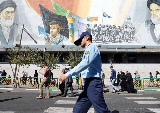 Un militaire iranien passe devant des photos du guide suprême iranien, l'ayatollah Ali Khamenei