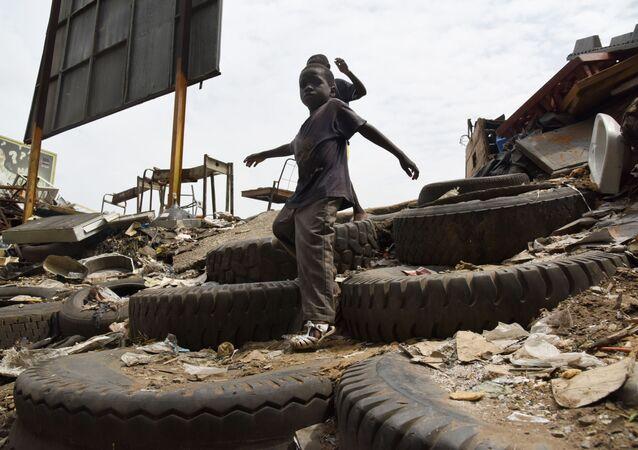 Des enfants descendent un escalier de fortune fait à base de pneus dans une décharge sauvage.