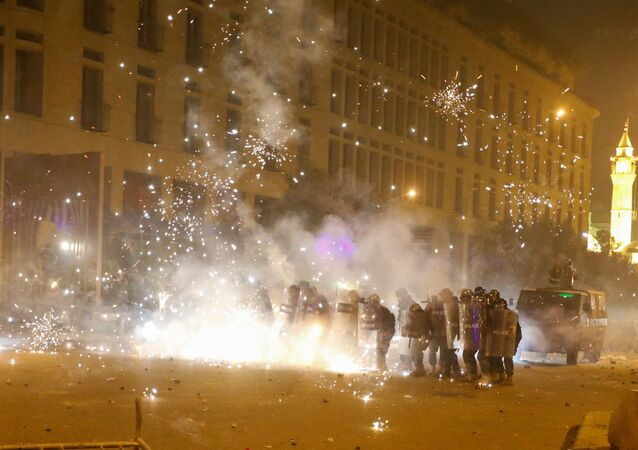 Des feux d'artifice sont déclenchés devant des policiers en position derrière des boucliers anti-émeute lors d'une manifestation contre une élite dirigeante accusée de conduire le Liban vers la crise économique à Beyrouth, Liban, le 18 janvier 2020.