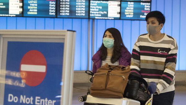 Des passagers portant un masque de protection dans l'aéroport de Los Angeles, le 22 janvier 2020. - Sputnik France