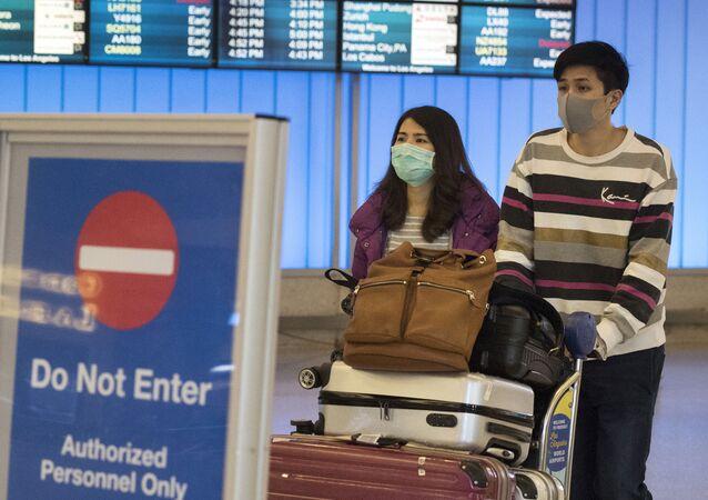 Des passagers portant un masque de protection dans l'aéroport de Los Angeles, le 22 janvier 2020.
