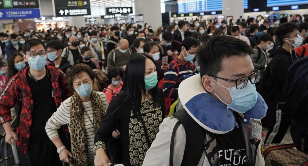 Passengers wear protective face masks at the departure hall of a high speed train station in Hong Kong