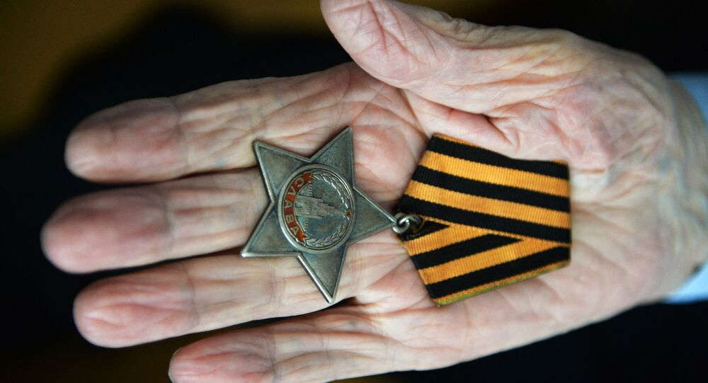 Nikolaï Titov, le  vétéran de la Seconde guerre mondiale, montre son ordre de la Gloire