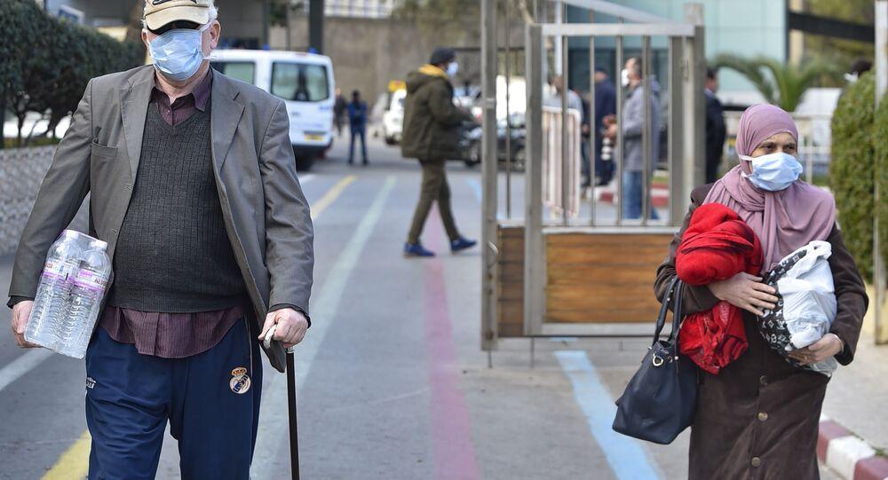 Des passants avec un masque de protection devant l'hôpital d'Alger, le 26 février 2020.