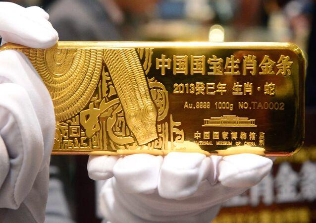 Une vendeuse tient une barre d'or dans une orfèvrerie à Pékin (image d'illustration)