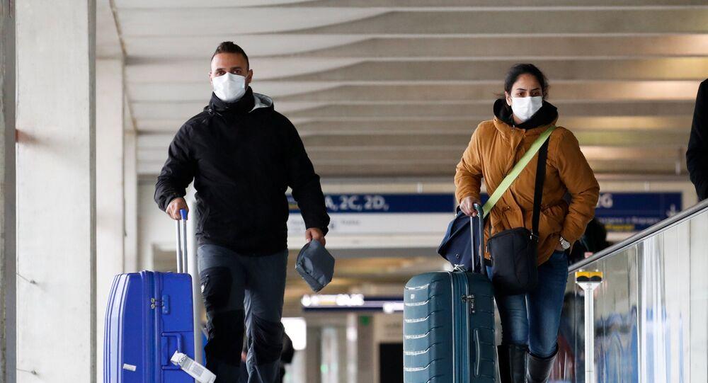 Les gens portant les masques protecteurs à l'aéroport de Roissy