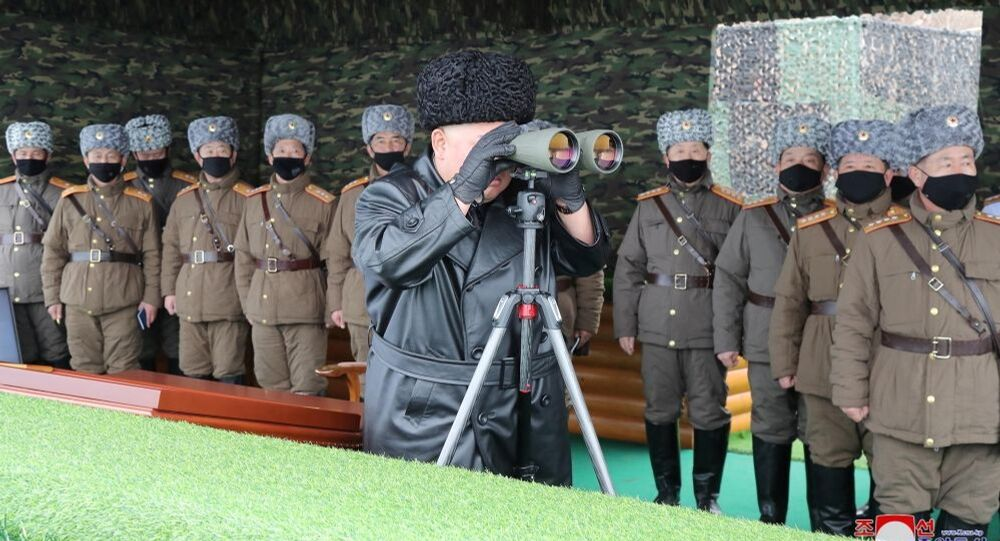 North Korean leader Kim Jong-un looks into binoculars during a missile test.