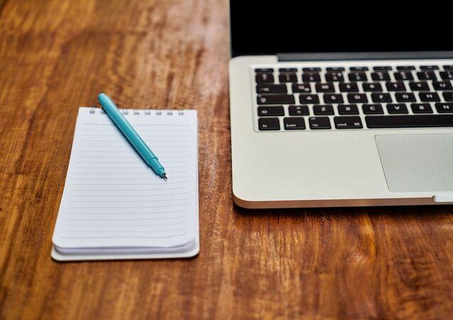 Un ordinateur portable et un carnet de notes