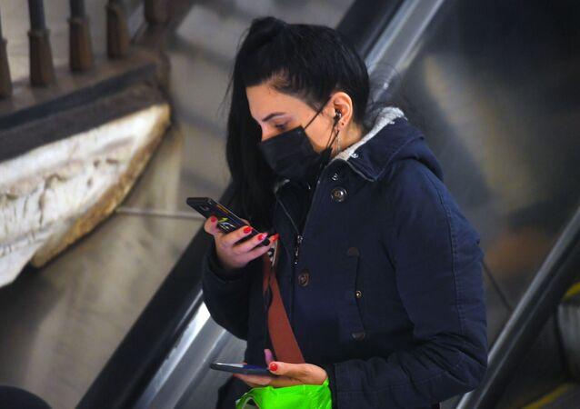 Une jeune femme portant un masque dans le métro de Moscou