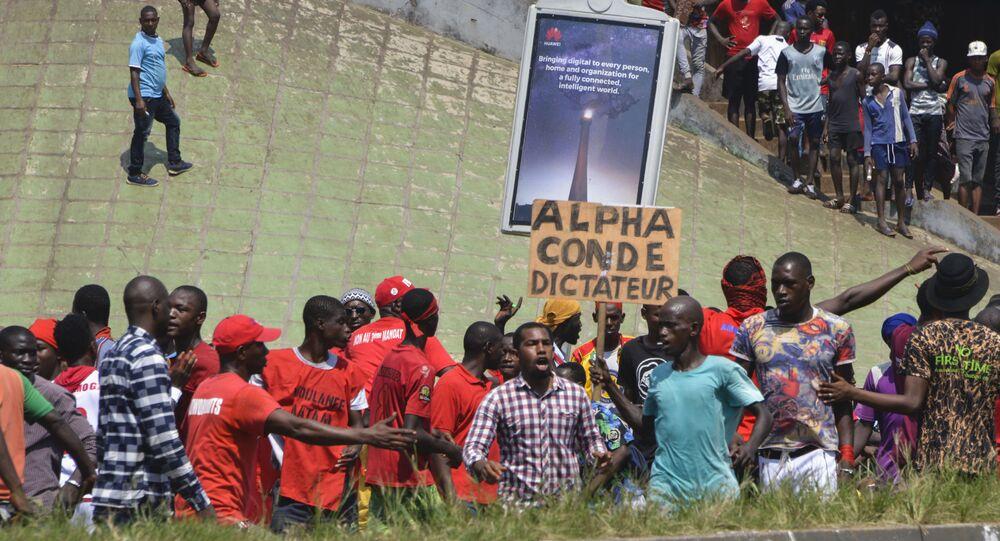 Un homme brandit une pancarte dénonçant la dictature d'Alpha Condé.
