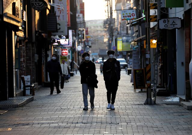 Pedestrians wearing masks amid the rise in confirmed cases of the novel coronavirus disease of COVID-19, make their way at a shopping district in Daegu, South Korea, March 4, 2020