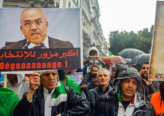 Des Algériens brandissent des pancartes contre l'ancien Premier ministre Ahmed Ouyahia.