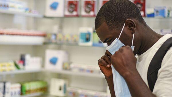 Un homme essaie un masque de protection, Zambie, février 2020. - Sputnik France
