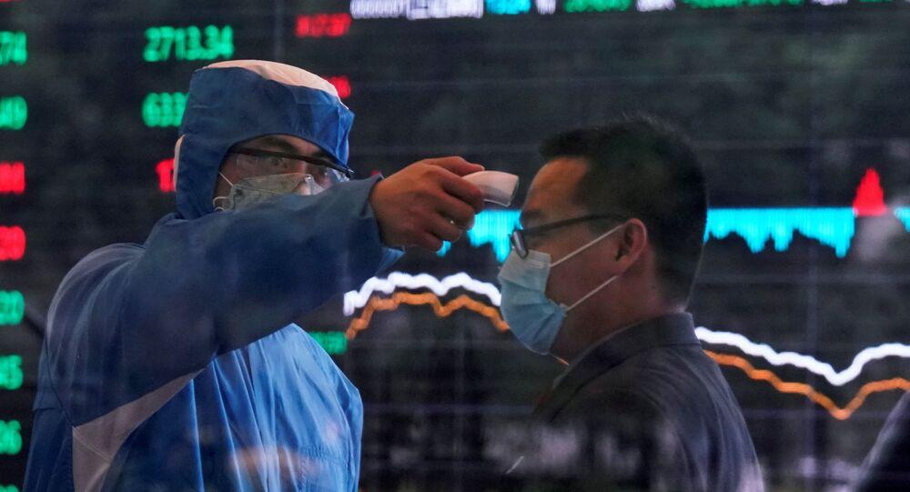 Un travailleur prend la température d'un homme à la Bourse de Shangaï