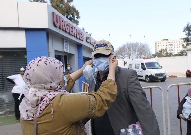 Des personnes portant des masques devant une clinique à Alger