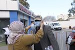 People wear masks stand outside a clinic where the flight crew as well as several people who were in contact with an Italian man who tested positive for COVID-19 went in for tests, in Algeria, Wednesday, Feb. 26, 2020.