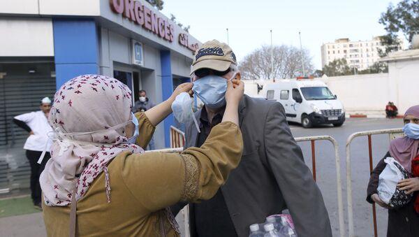 Des personnes portant des masques devant une clinique à Alger - Sputnik France