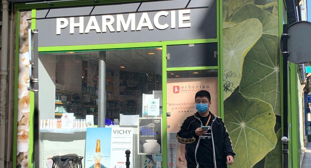 Un homme en masque devant une pharmacie en France