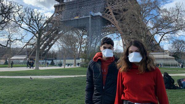 Des gens portant des masques se réposent au pied de la Tour Eiffel - Sputnik France