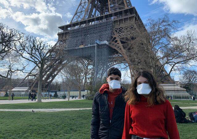 Des gens portant des masques se réposent au pied de la Tour Eiffel