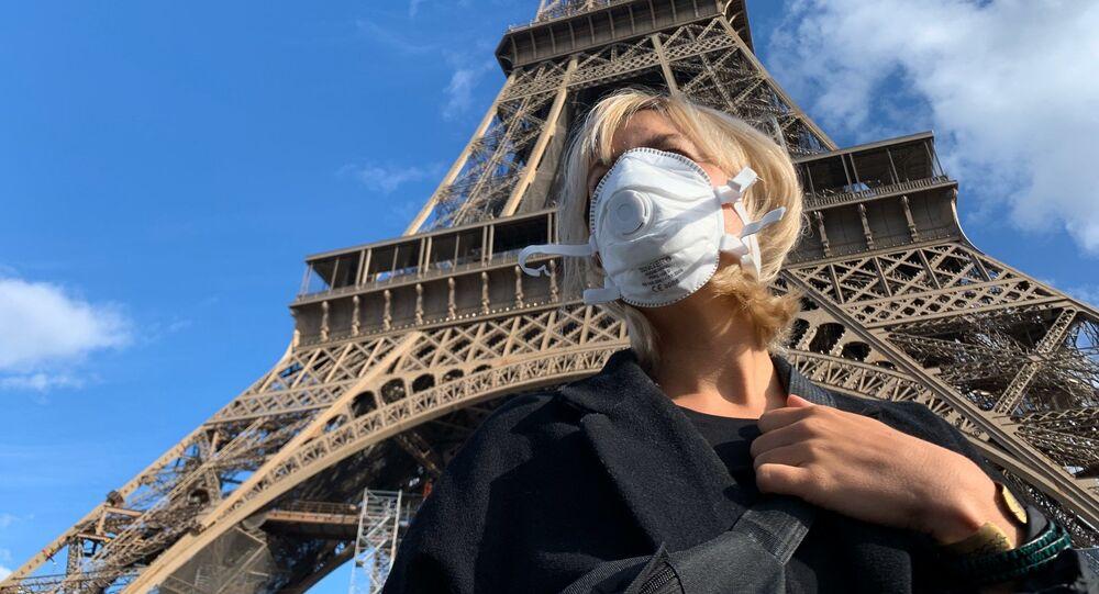 Une femme portant un masque au pied de la Tour Eiffel