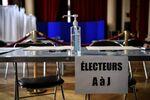 Un flacon de gel hydroalcoolique dans un bureau de vote.