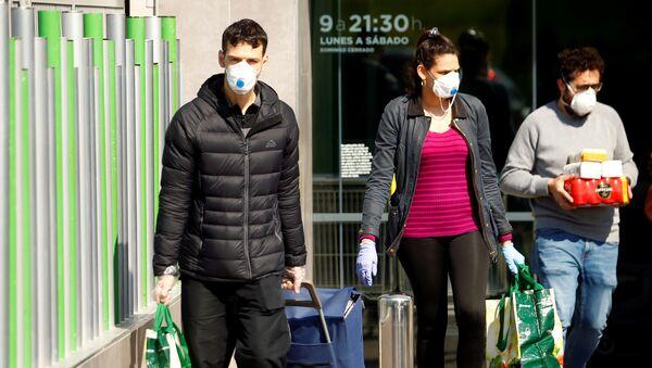 People wearing protective masks walk out of a supermarket, amidst concerns over Spain's coronavirus outbreak in central Madrid - Sputnik France