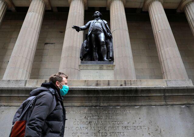 Un homme en un masque chirurgical marche devant une statue du premier président américain George Washington
