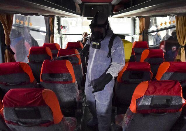 Un agent municipal désinfecte un bus contre le coronavirus à la station Kherrouba à Alger