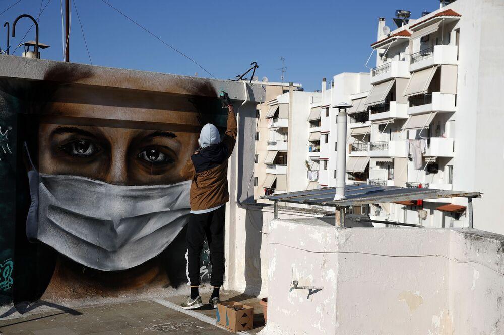Un jeune artiste grec réalise un graffiti à l'effigie d'une femme portant un masque.
