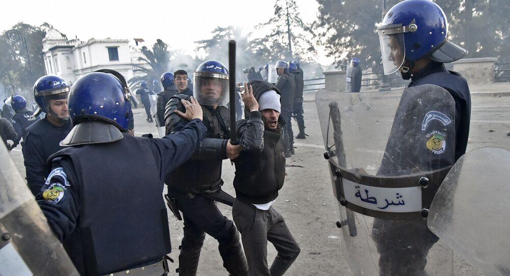 Les membres des forces de sécurité algériennes interpellent un manifestant.