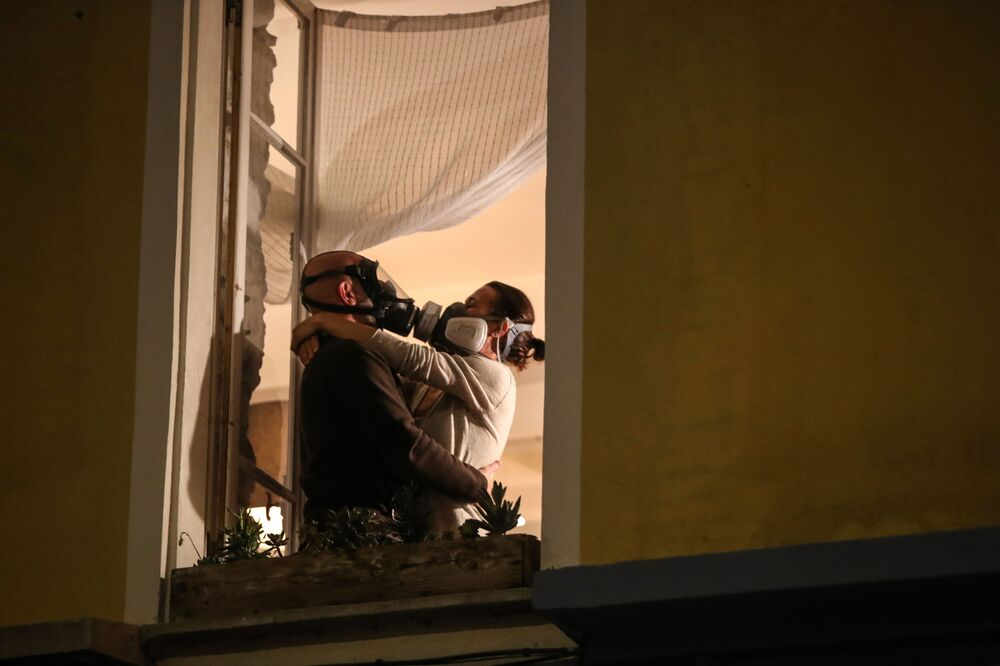 Un homme et une femme en masques à la fenêtre à Nice, le 24 mars 2020