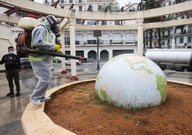 Un travailleur vêtu d'une combinaison de protection désinfecte une sculpture en forme de globe, à la suite de l'épidémie de coronavirus (COVID-19), à Alger, en Algérie, le 23 mars 2020.