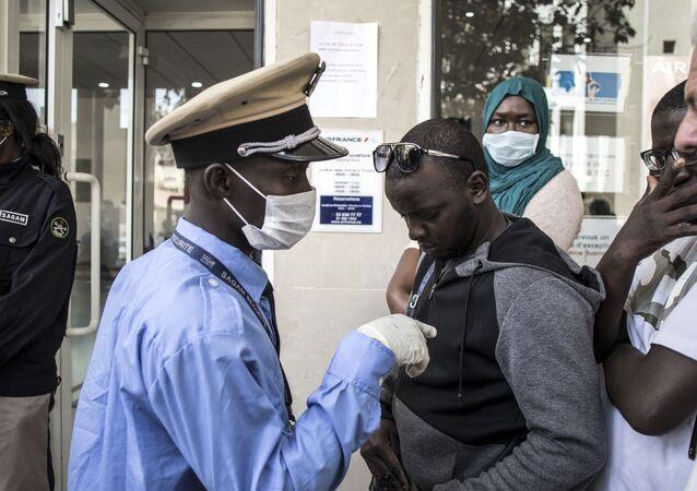 Des personnes font la queue devant le bureau d'Air France à Dakar, le 19 mars 2020.