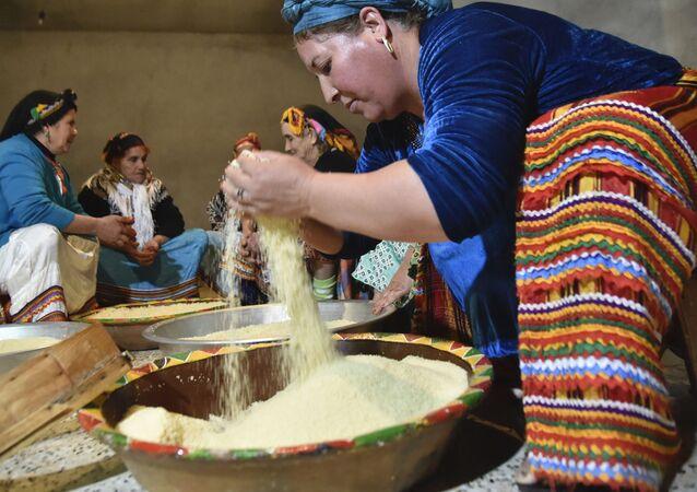 Une femme prépare la semoule pour le couscous