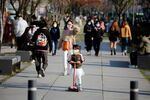A girl wearing a protective face mask to prevent contracting the coronavirus disease (COVID-19) rides a toy kick scooter at a park in Seoul, South Korea, April 3, 2020