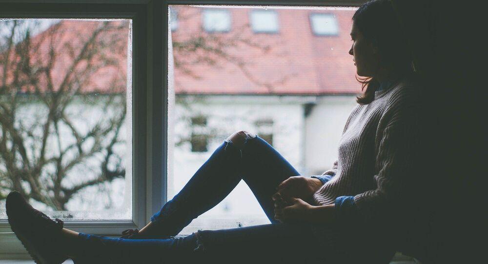 Une jeune femme regarde par la fenêtre