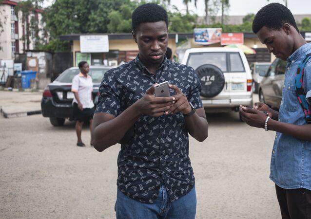 Deux jeunes scrutent leur téléphone portable.